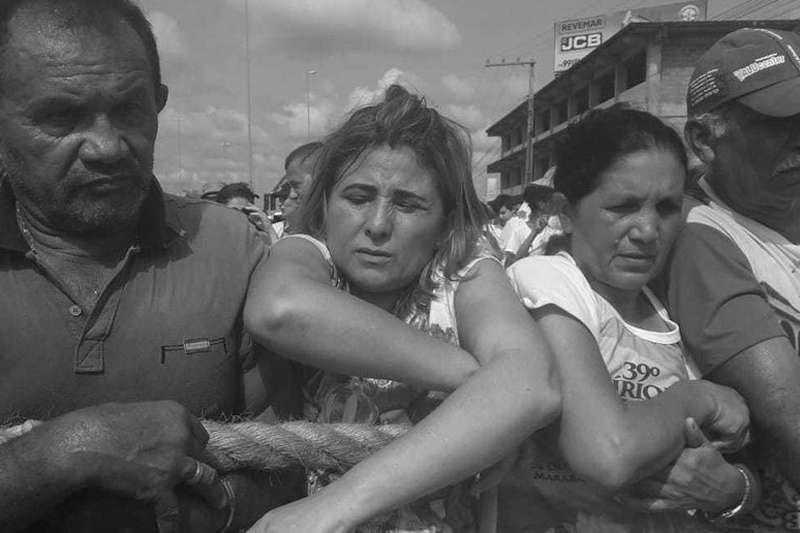 De braços cruzados, Maria José Barbosa acompanha a procissão segurando na corda e pés descalços
